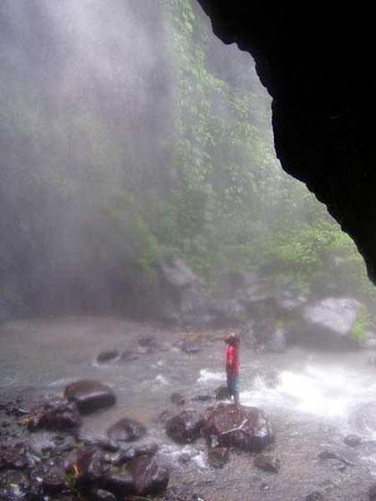 Auf einem Felsblock mitten im Bergbach steht ein Mann und betrachtet den Wasserfall