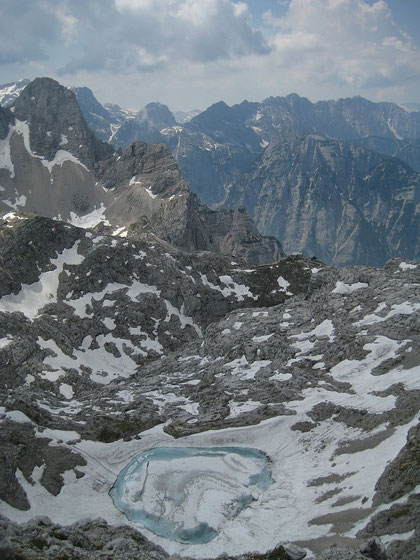 Der obere Krizsee mit der Pogacnik Hütte (rechts im Grünen) und dem Pihavec (links)