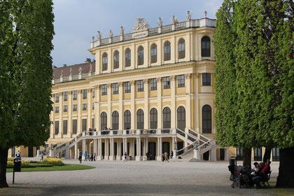 Ein kurzer Blick durch die langen Pfade des Schlossparks Schönbrunn auf die Fassade des schönsten Schlosses Wiens.