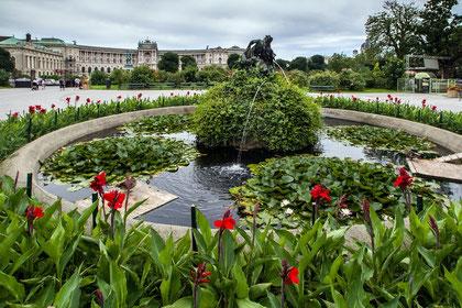 Eine runder flacher Brunnen umgeben von Grün, Seerosen und roten Blumen mit einer Skulptur in der Mitte.