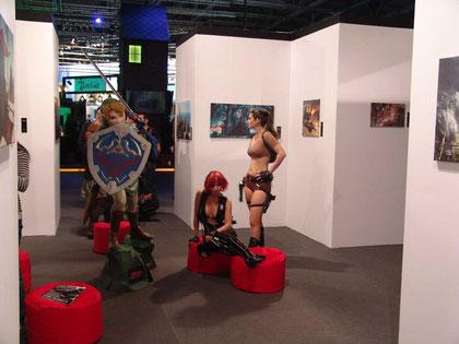 Zwei Models und Link posieren auf der Games-Art-Ausstellung von Aruba Events. Links unten im Bild: ein elektrospieler.