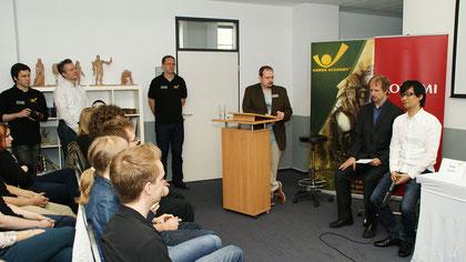"""Unser Kollege Thomas Nickel (am Pult) ist stolz auf den hohen Besuch: """"MGS""""-Mastermind Hideo Kojima (rechts außen im weißen Hemd) beehrt die Studenten und Dozenten der Games Academy in Frankfurt."""