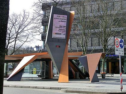 """Aachen, Bushaltestelle am Friedrich-Wilhelm-Platz (Elisenbrunnen), vom Architekten Peter Eisemann 1998 für Aachen entworfen wegen der Form vom Aachener Volksmund (Öcher) einfach """"Frittezang"""" genannt."""
