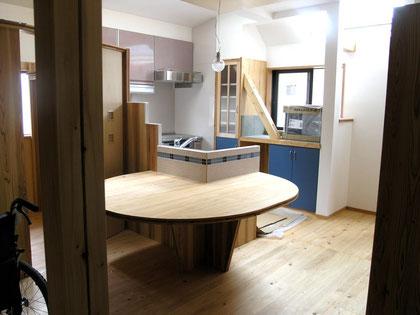 改修後のダイニングキッチン。シンクの端に楕円のテーブルをつくりました。左側に収納スペースを設けてあります。ななめの材木は新しく設置した筋違です。