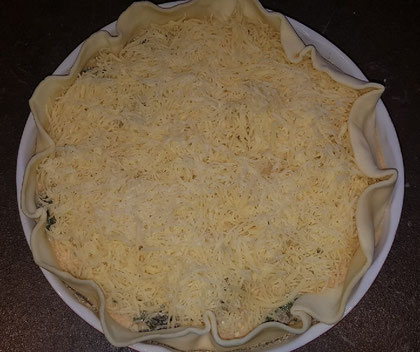 geriebener Käse auf einer Mürbeteig Quiche mit Mangold Füllung