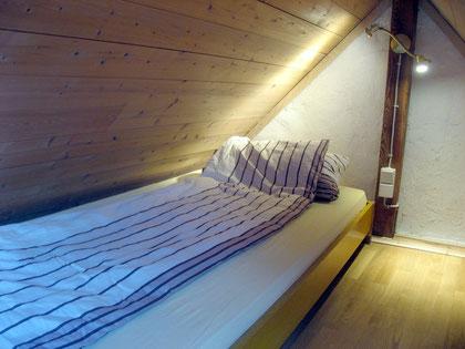 Einzelbett auf Schlafboden, nur über Leiter erreichbar.