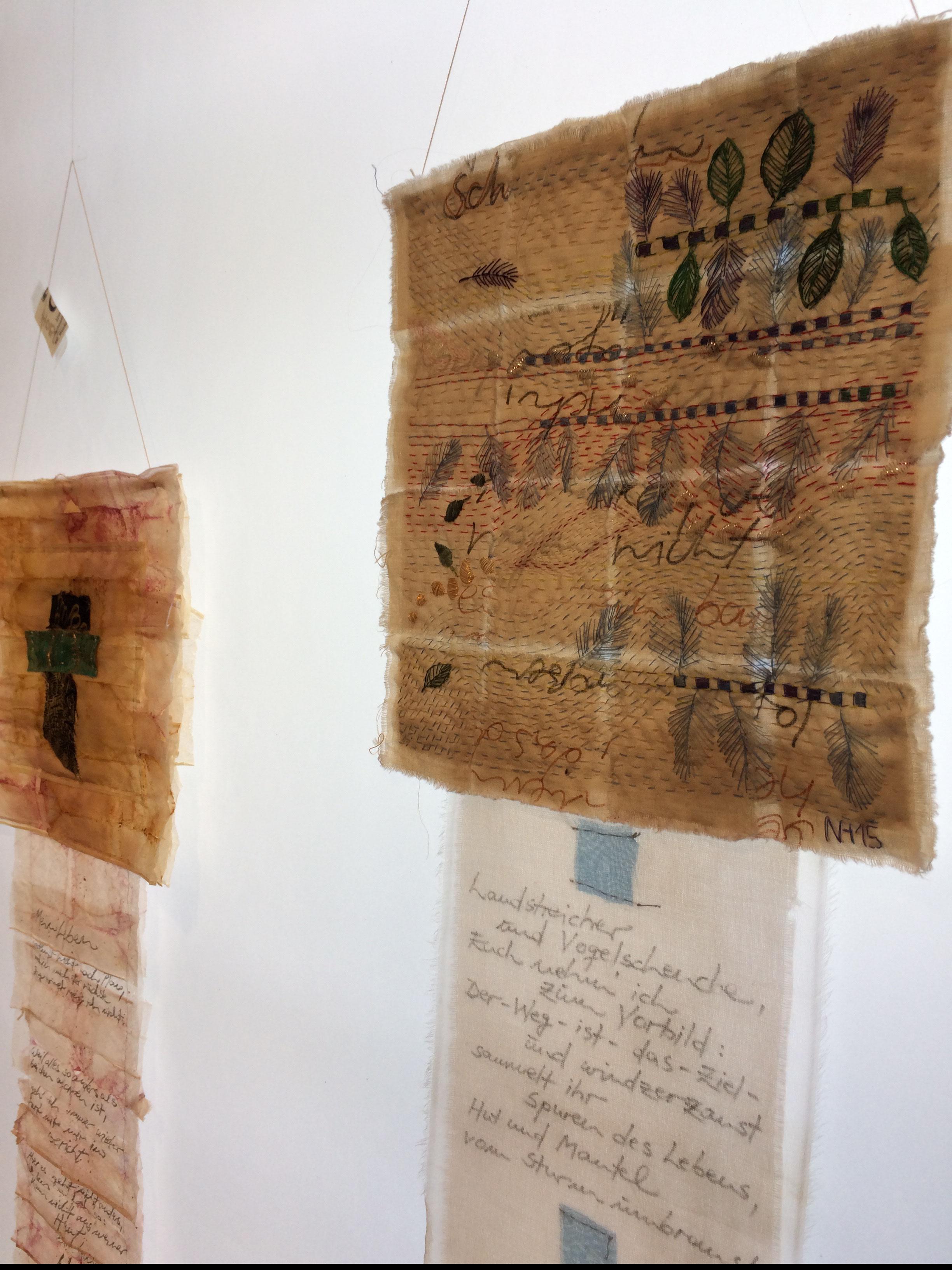 """Zwei handbestickte Fahnen von Nadja Hormisch, links """"My new HOBO-Skin"""", rechts """"My new BORO-Skin"""". Beide Fahnen aus pflanzengefärbtem Abaca-Papier, Seide und Baumwolle."""