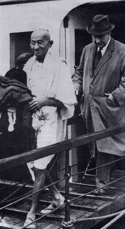 Mahatma Gandhi disembarking from the ferry at Folkestone, UK., with a British Government official.