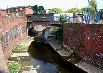 Photograph of the canalised River Rea near the site of Vaughtons Hole. The photograph was taken from Belgrave Middleway. The bridge carries Gooch Street.