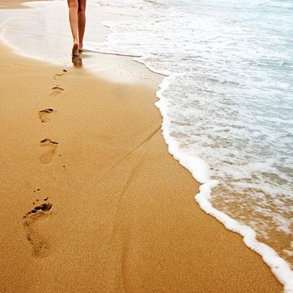 Füße am Meer im Sand und Wellen
