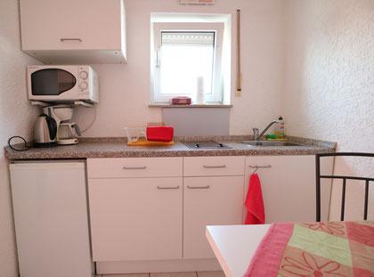 ...Küchenbereich mit Herd, Kühlschrank und Sitzgelegenheit...