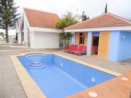 Vor dem Gästehaus das zum  Chalet gehört sieht man den Pool vom Grundstück. Das Chalet und Gästehaus sind mit einem Spitzdach gebaut .