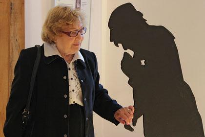 Paula Calder ergreift die Hand ihrer Mutter, die als Schattenriss dargestellt ist und dem Holocaust zum Opfer fiel.