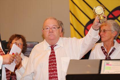 Stolz streckt Reené den Pokal in die Höhe, den er soeben vom Präsidenten erhalten hat.