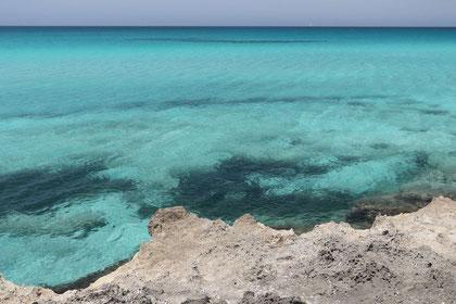 Kleines Stück schroffer hellgrauer Felsen an der Punta della Suina mit durchsichtigem türkisfarbenem Meerwasser
