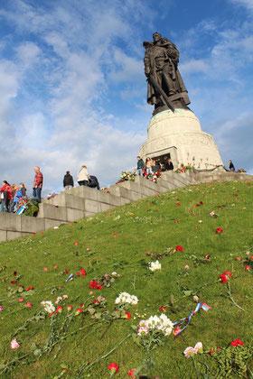 """Hügel mit nieder gelegten Blumen auf dem Rasen, oben Skulptur """"Rotarmist mit Kind"""". 9.Mai Sowjetisches Ehrenmal Treptower Park. Foto: Helga Karl"""