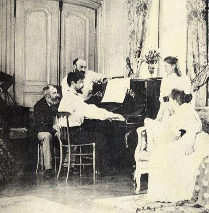 Debussy al piano. Tras él, el compositor Ernest Chausson