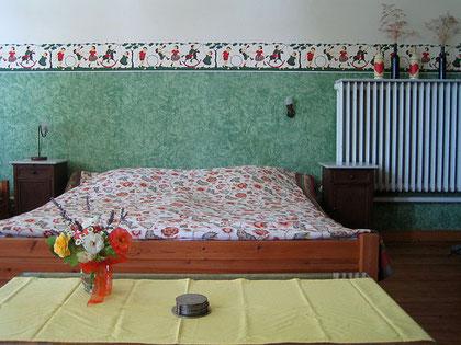 Das Doppelbett vor der restaurierten Wandbemalung