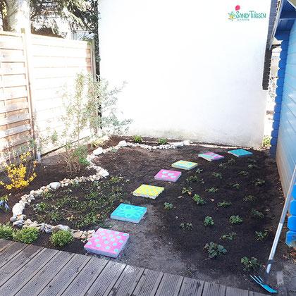 nachher - neu bepflanzt und mit bunten Trittsteinen