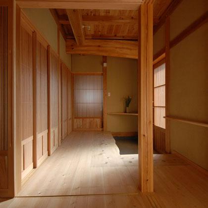 玄関から続く無垢材の木目が美しい広い廊下