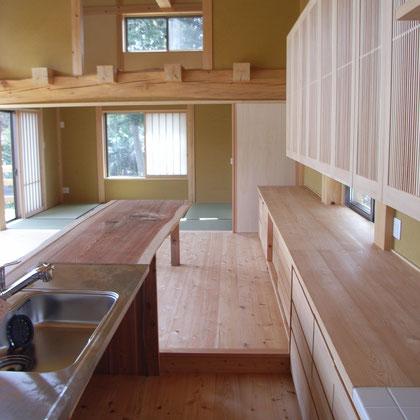 オープンキッチンに続く一枚板のテーブル。木製建具も木組みに家にマッチしている。