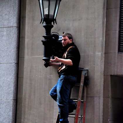 Guy fixing lamp in the Financial District