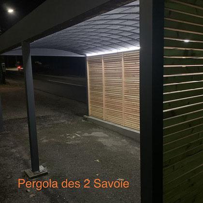 Ruban LED et brise vue en douglas sous un carport en aluminium sur mesure. Personnalisez vos abris, fini le givre en hiver et la surchauffe en été.