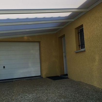Une structure en aluminium avec une toiture en polycarbonate opale réfléchissant qui protège la porte d'entrée et qui permet de stationner à l'abri
