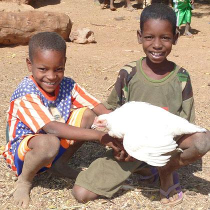 Des parents contents du parrainage offrent un coq à AGE-ASOPO, remarquable générosité de gens pauvres