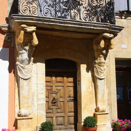 Bild: Eingang des Karyatiden Haus mit Balkon, gestützt von zwei Frauenfiguren in Saint-Saturnin-lés-Apt