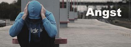 Mann auf Bahnsteig hält sich Ohren zu