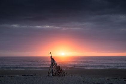 """Sonnenuntergang am Kohaihai River Mouth. Die Tourismusbehörde der Region """"West Coast"""" beschreibt die Farben der Sonnenuntergänge als """"zu intensiv für jeden Instagram Filter."""""""