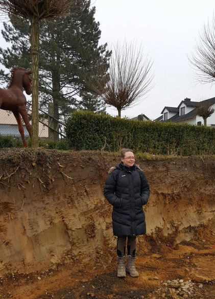 Lebensgröße Yvonne - sie steht im zukünftigen Reitplatz, im Hintergrund die Einfahrt.