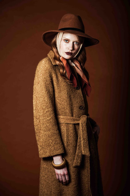 Fashion portrait of a red hair model with a hat and a coat
