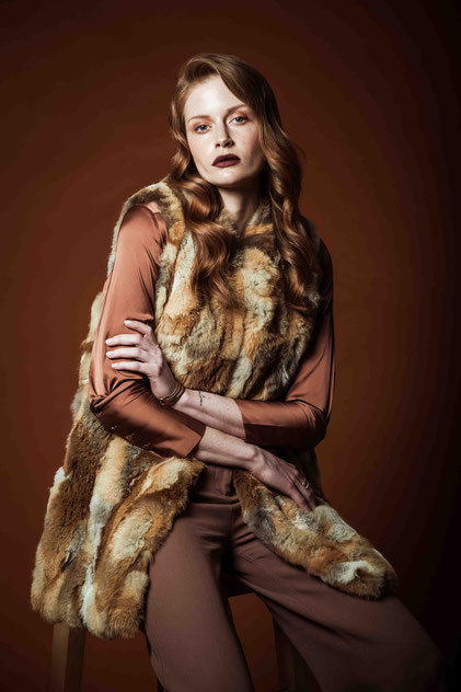 Fashion portrait of a red hair model with a fake fur