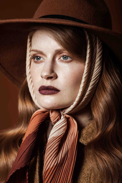 Fashion portrait of a red hair model with a hat