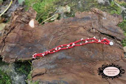 Fin bracelet double rang crocheté à la main, coton rouge et perles de rocaille banches, il se ferme par une boule de perles à glisser dans un maillon perlé