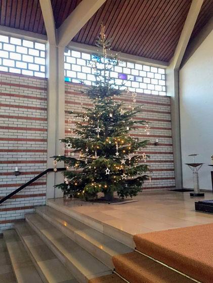 ein großer Weihnachtsbaum wird am letzten Verkaufstag in der Kirche aufgestellt