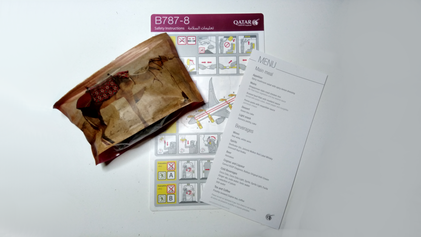 Amenity kit, menu and a safety card from QR841