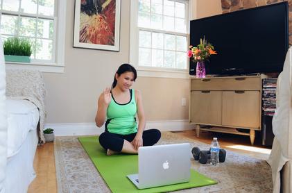 Junge Frau sitzt auf Yogamatte vor Laptop und lernt Entspannung