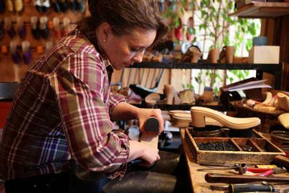 Cette image représente un maître artisan qui travaille le cuir dans son atelier