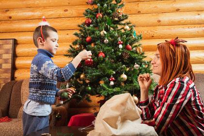 Mutter und Sohn dekorieren den Weihnachtsbaum, die Erinnerung an solche Weihnachtstraditionen hat immer wieder Schriftsteller und Künstler zu ihren Werken inspiriert.