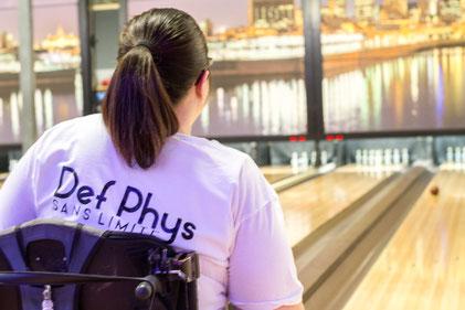Femme portant un chandail avec le logo de l'organisme qui joue au bowling en fauteuil roulant.