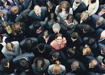 Imagen con personas mirando hacia el suelo y una hacia la foto, en el centro