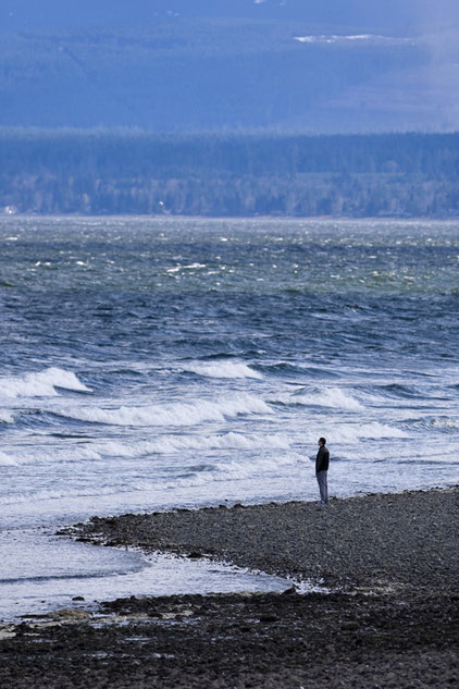 A man watching stormy waves at Point Holmes Park in Comox.