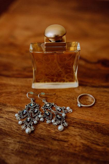 Brautschmuck und Parfum auf dem Holztisch