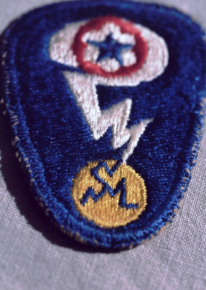 Army personnel of the Manhattan Project wore this shoulder patch, picturing a question-mark-shaped lighting bolt splitting something obviously globular. An atom? The world?
