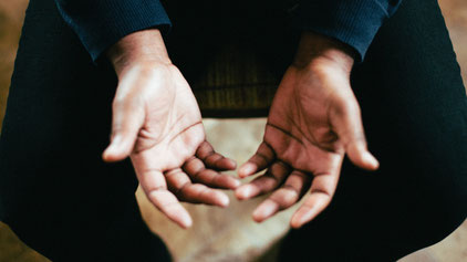 A man holds his hands open in prayer