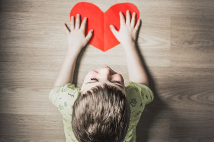 Boy touching paper heart at a table