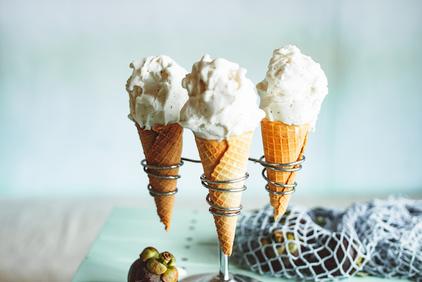 バインダーファイルに挟まれたレポート用紙とボールペン。メモ帳とクリップ、眼鏡、コーヒーの入ったマグカップ。観葉植物のグリーン。